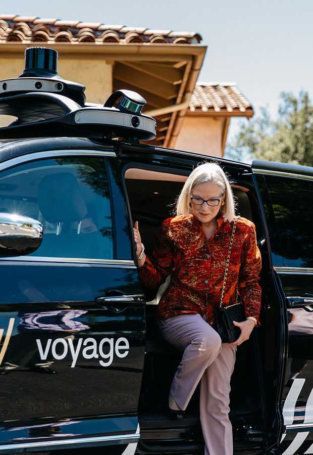 Woman getting out of a Voyage automated vehicle